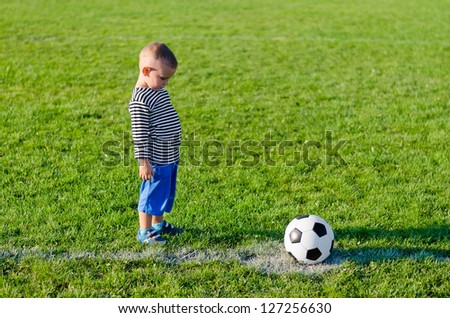 Little boy psyching himself up about to kick a soccer ball off the centre mark on a green grassy sportsfield in soft evening light