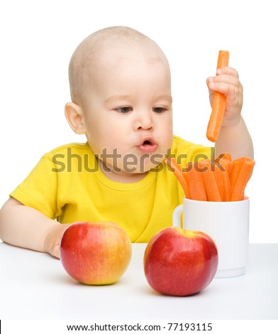 Little boy pulling up carrot from a cup, isolated over white - stock photo