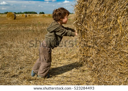 Little boy pushes stack of hay