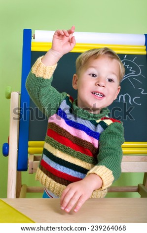 little boy put his hand up in school - stock photo