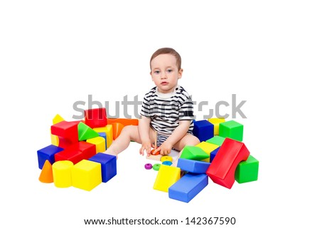 Little boy puts colored cubes and pyramid isolated on white background - stock photo
