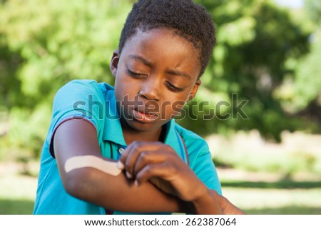 Little boy putting plaster on arm on a sunny day