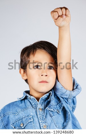 Little boy raising his hand as a sign of rebellion - stock photo