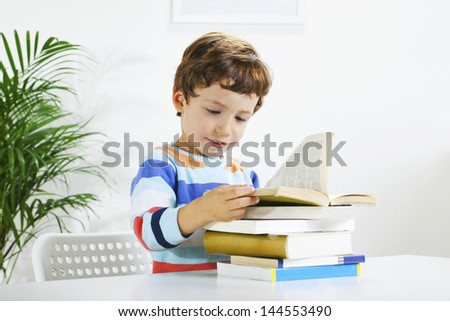 Little boy reading a book./ Schoolboy studying in home. - stock photo