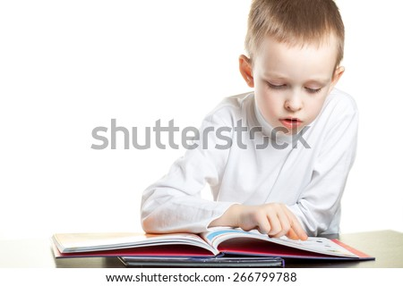 little boy reading a book with interest