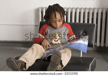 Little boy reading a magazine