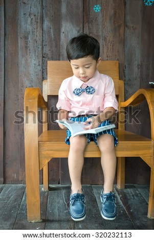 little boy reading and  looking at book .