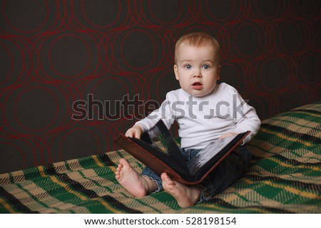 little boy reading book at home