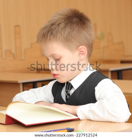 little boy reading book in the classroom - stock photo