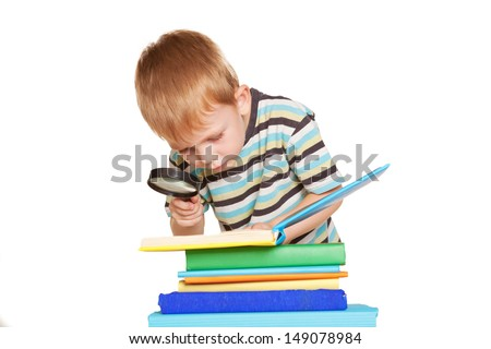 Little boy reading book with a magnifying glass. Isolated on white background. - stock photo