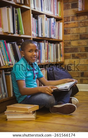 Little boy reading on library floor at the elementary school - stock photo