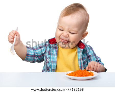 Little boy refuses to eat making unpleasant grimace, isolated over white - stock photo
