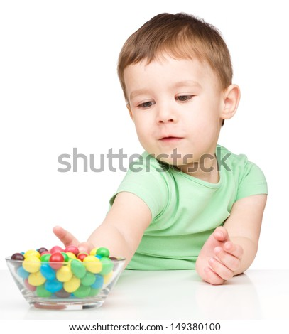Little boy refusing to eat colorful candies, isolated over white - stock photo