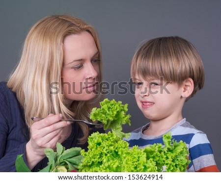 Little boy  refusing to eat green salad  - stock photo
