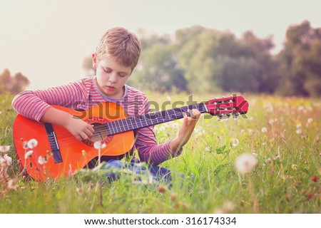 Little boy rehearsing on his acoustic guitar - stock photo