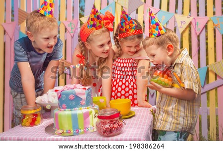 Little boy rejoice  in his birthday round about her friends - stock photo