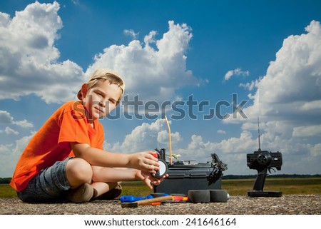 Little boy repairer the radio control car outdoor near field - stock photo