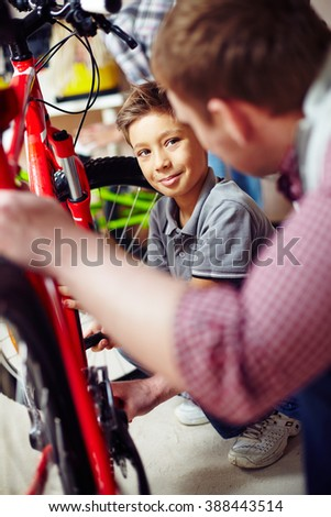Little boy repairing his bicycle with the help of his father - stock photo