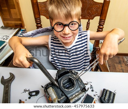 Little boy repairing photocamera