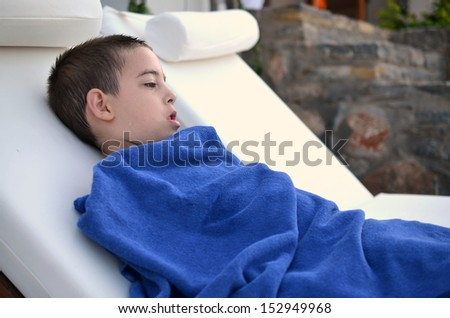 Little boy resting by the pool - six year old boy wrapped in a towel resting after a swim in the oceanside pool on the Greek island of Crete - stock photo