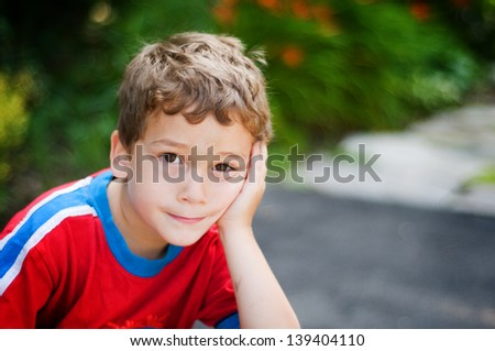 little boy resting his face in his hand looking at the camera with a bored expression - stock photo