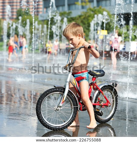 Little boy rides his bike among fountains in summer day - stock photo