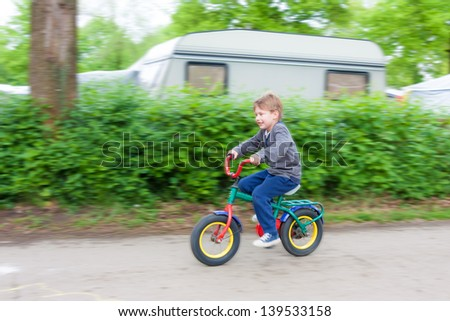 Little boy riding a bicycle on a camping park - stock photo