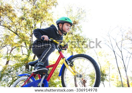little boy riding a bike in the park
