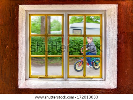 Little boy riding a bike outside the house - stock photo