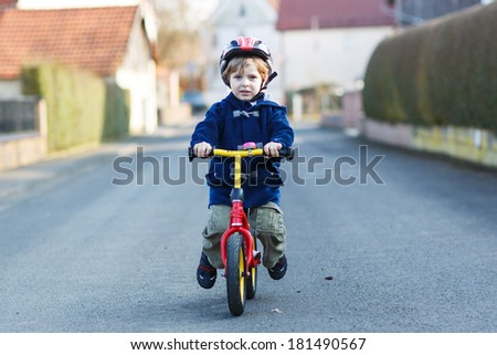 Little boy riding bicycle in village or city.