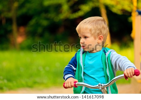 little boy riding bike in the park - stock photo