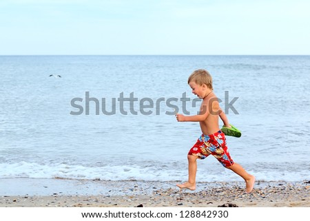 Little boy running at the shore near the sea
