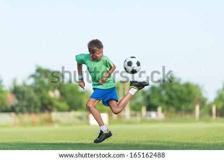 little boy running dribbling on the sports field - stock photo
