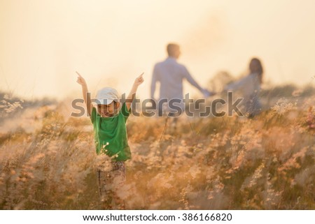 Little boy running on meadow with sunset - stock photo