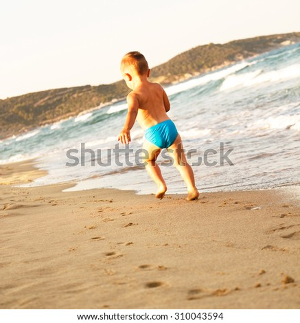 Little boy running on the shores of a sandy beach at sunset - stock photo