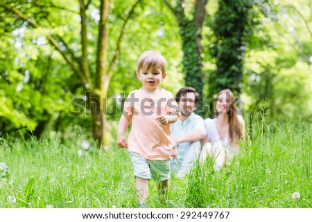 Little boy running over meadow with family in back