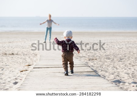 Little boy running to his mom on the beach. - stock photo