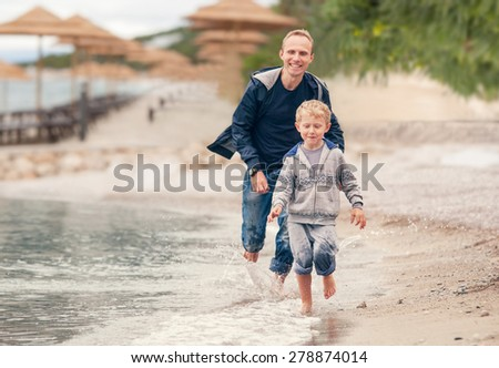 Little boy running with his father at the surf line - stock photo