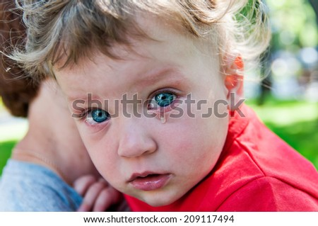 little boy's crying at her mother in her arms - stock photo