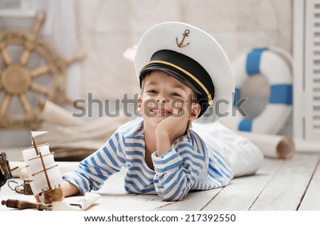 Little boy-sailor played in a naval battle in his room - stock photo