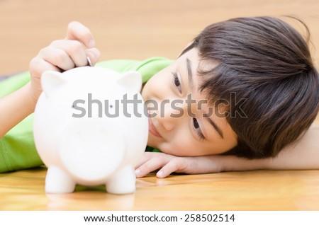 Little boy saving money in piggy bank  - stock photo