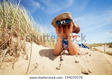 Little boy searching with binoculars at the beach dressed as explorer concept for nature, discovery, exploring and education - stock photo