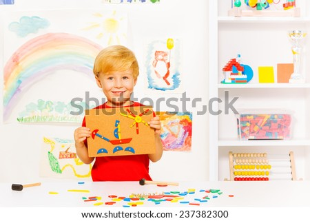 Little boy show blocks and nail picture of ship - stock photo
