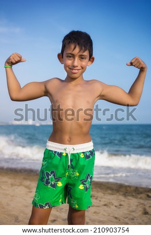 little boy showing his muscles on the beach - stock photo