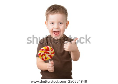 little boy shows his thumb and smiling while holding a piece of candy in his hand - stock photo