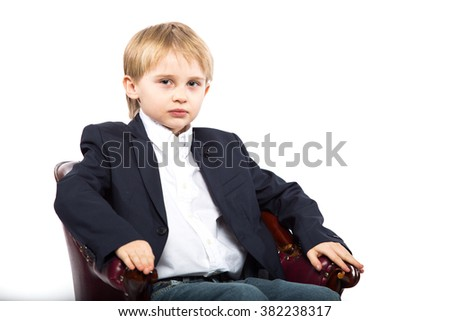 Little boy shows the president sitting in an expensive chair. Isolated on white background. Shooting in the studio