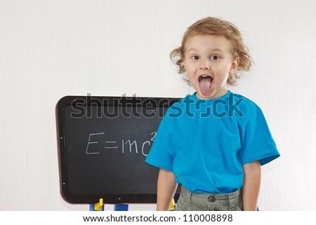 Little boy shows tongue near formula on a blackboard - stock photo