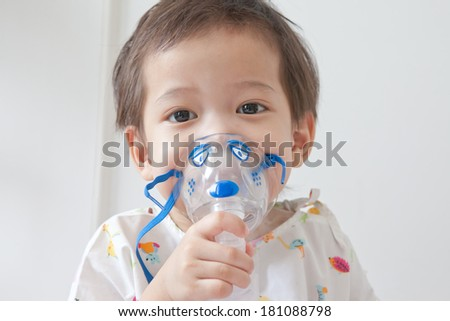 Little boy sick in hospital with a respiratory mask - stock photo