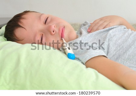 Little boy sick. It lies in pastels and measures the temperature - stock photo