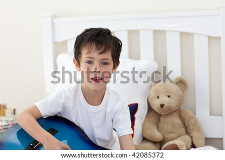 Little boy singing and playing guitar in the bedroom